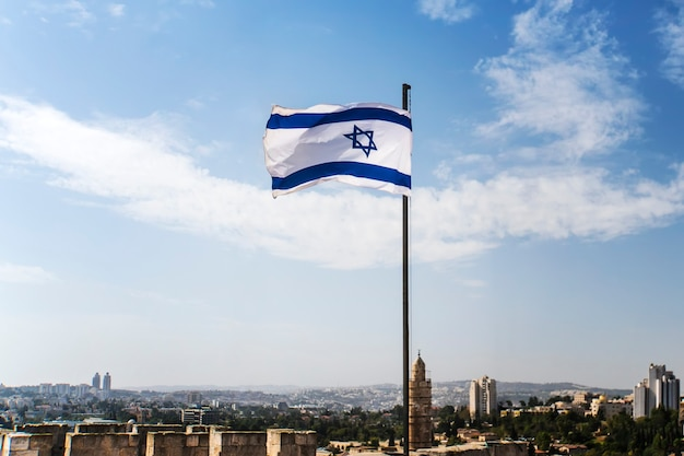 Israel flag flapping in the wind at good sunny day and old city background.