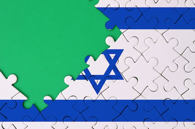 Israel flag  is depicted on a completed jigsaw puzzle with free green copy space on the left side