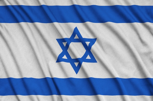 Israel flag is depicted on a sports cloth fabric with many folds.