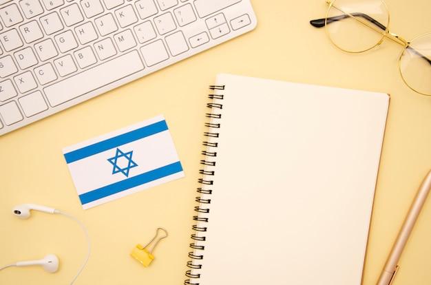 空のノートブックの横にあるイスラエル国旗