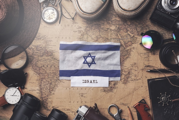 Israel flag between traveler's accessories on old vintage map. overhead shot