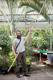 대나무 통나무를 손에 들고 있는 이스라엘 남자. 대형 슈퍼마켓, 정원 센터에서 대나무를 사는 미국 백인 수염 남자의 초상화. 러시아 구매자는 나무 가게에서 대나무로 장식용 울타리를 선택합니다.
