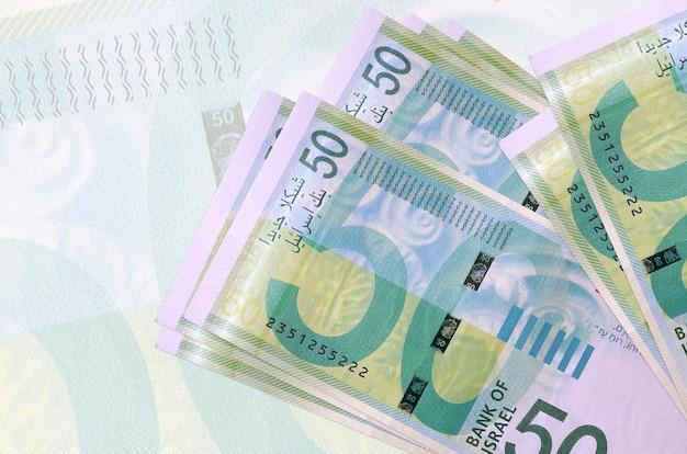 Israeli new shekels bills lie in stack on background
