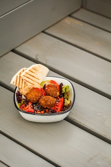 Israeli street food. falafel salad with hummus, beetroot and vegetables in bowl in a restaurant.