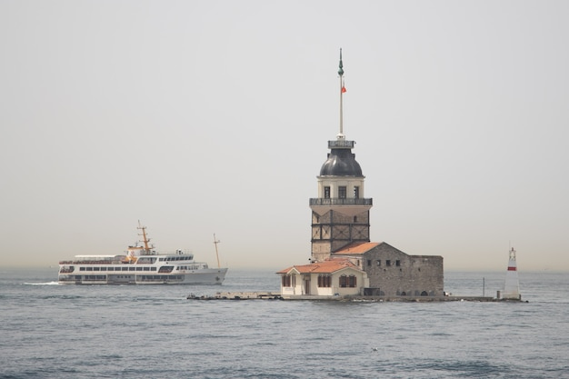 Istanbul, turkey - august 08, 2021: a view of istanbul maiden tower kiz kulesi and boat at bosporus