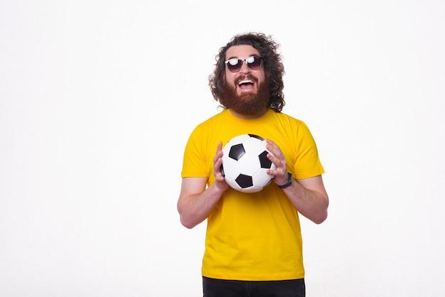 Время футбола. бородатый мужчина держит футбольный мяч.