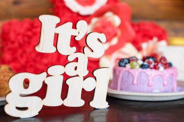 フレッシュベリーとヨーグルトクリームと木製看板「it a girl」の甘いチーズケーキ。ベビーシャワーパーティーのお菓子。