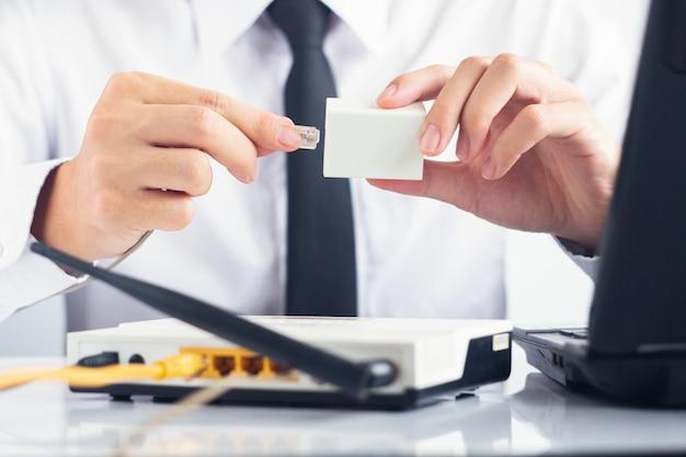 男性itサポート、adslスプリッターとモデムおよびラップトップを白いテーブルに接続するrj11ケーブルを保持