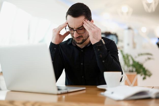 動作しません!疲れた男性プログラマーがこめかみをマッサージし、頭を抱えてコードのエラーを探しています。カフェでコーヒーを飲むリモートまたはフリーランサーの労働者。