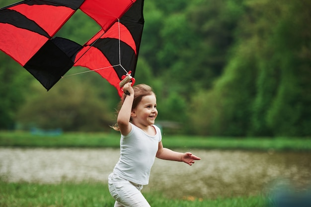 It feels awesome. positive female child running with red and black colored kite in hands outdoors