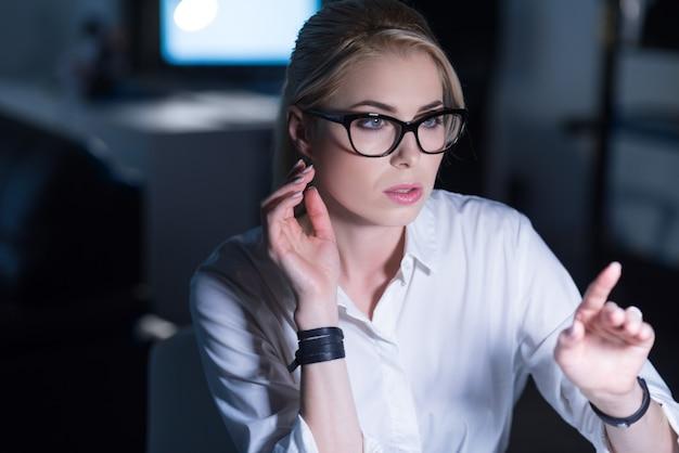 일하는 it 소녀. 사무실에 앉아서 관심을 표명하면서 현대 기술을 사용하는 유쾌한 기뻐 집중된 여성