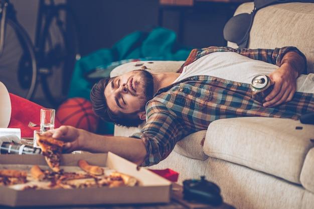 긴 밤이 되었습니다. 젊고 잘생긴 남자가 피자 조각과 맥주와 함께 소파에서 기절했다