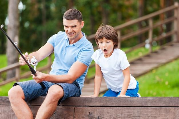 Это большая рыба! счастливые отец и сын вместе ловят рыбу, пока маленький мальчик выглядит взволнованным и держит рот открытым