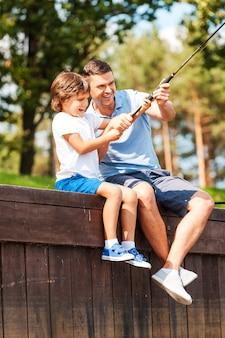 Это большая рыба! счастливый отец и сын вместе ловят рыбу, сидя на набережной