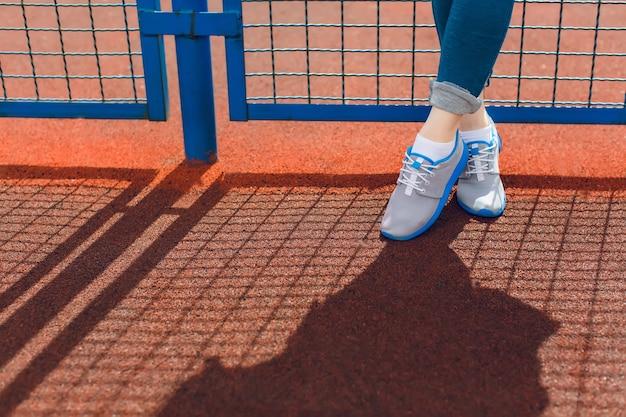 スタジアムの青いフェンスの近くに立っている少女の足の写真です。彼女はブルーのラインとブルーのパンツが入ったグレーのスニーカーを着ています。