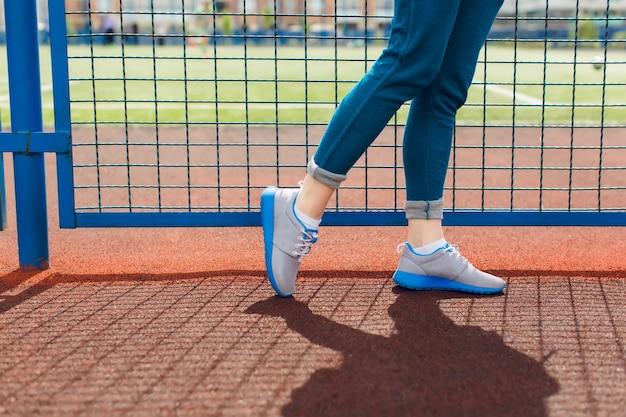 スタジアムの青いフェンスの近くを歩く少女の足の写真です。彼女はブルーのラインとブルーのパンツが入ったグレーのスニーカーを着ています。