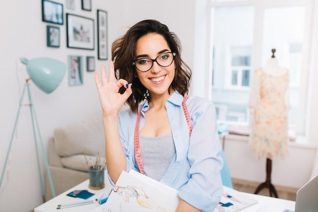 Это портрет брюнетки в сером платье и голубой рубашке, стоящей у стола в мастерской студии. в одной руке она держит эскизы. она делает пальцами знак