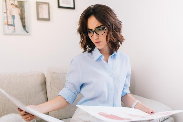 スタジオのソファーに座っているブルネットの少女の肖像画です。彼女は青いシャツと白い時計を着ています。彼女は両手で持っているスケッチに興味があります。