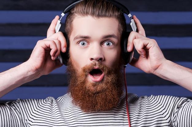 놀라운 노래입니다. 헤드폰을 끼고 수염을 기른 자신감 있는 청년이 벗겨진 배경에 서서 음악을 듣고 있다