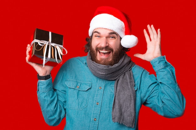 Пришло время рождества. удивленный мужчина держит подарочную коробку.