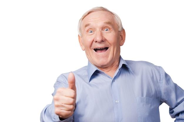 Это круто! возбужденный старший мужчина протягивает руку с большим пальцем вверх, стоя на белом фоне