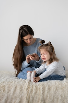 It is difficult to work remotely at home. young beautiful mother sits at home on a sofa. mobile phone in the hands. little tearful daughter near mother. the child is suffering