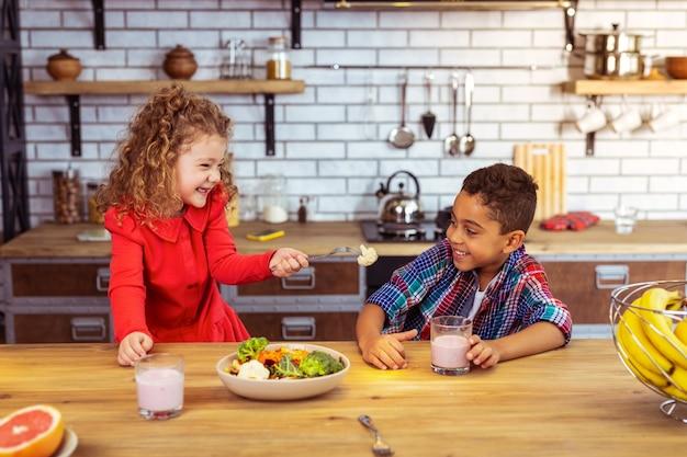 Это вам. красивый интернациональный ребенок с улыбкой на лице смотрит на цветную капусту