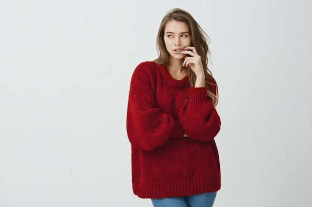 It is hard to refrain from sweets. good-looking girl office worker in loose red sweater holding fingers in lips while looking aside with curiosity or interest, being on diet and dreaming about burger