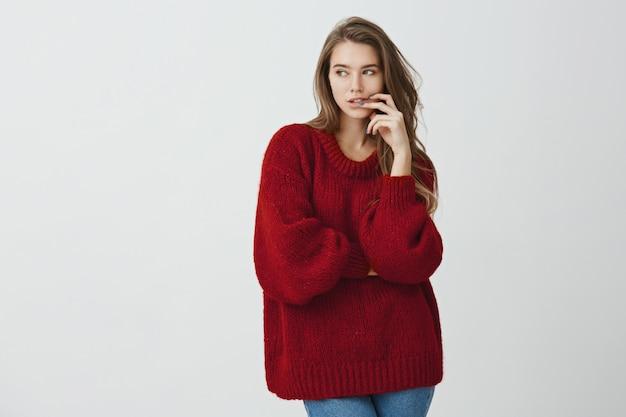 Трудно воздерживаться от сладостей. красивая офисная работница в красном свитере держит пальцы в губах, с любопытством или интересом смотрит в сторону, сидит на диете и мечтает о бургере
