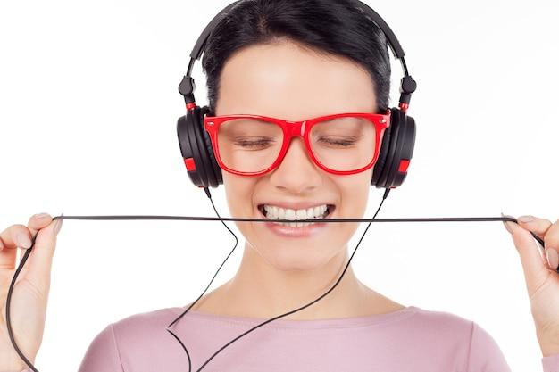 그녀가 가장 좋아하는 노래입니다. 빨간 안경을 쓰고 헤드폰을 끼고 음악을 듣고 눈을 감고 있는 아름다운 젊은 여성