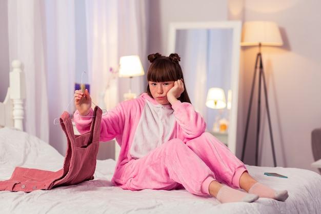Настало время. скучно девушка сидит на своей кровати и демонстрирует мягкое платье
