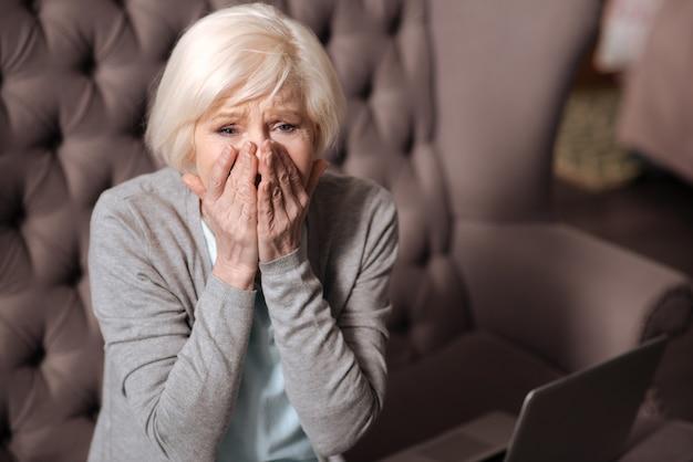 불가능하다. 집에 앉아있는 동안 수석 여자 느낌 충격의 초상화를 닫습니다.