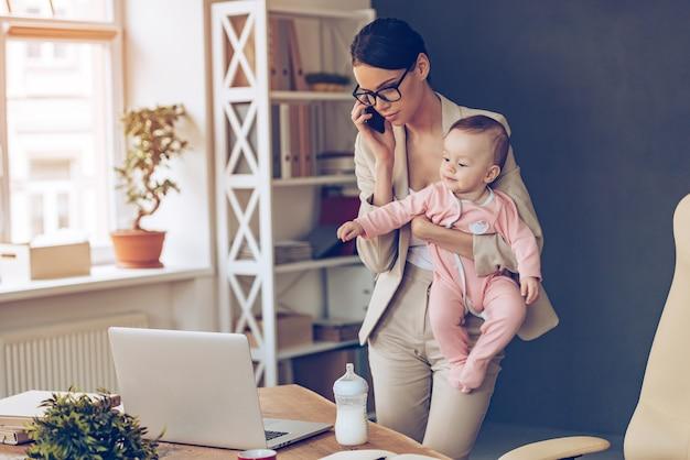 워킹맘 쉽지 않아요! 그녀의 작업 장소에서 그녀의 아기 소녀와 함께 서있는 동안 휴대 전화로 얘기하고 노트북을보고 젊은 아름다운 사업가