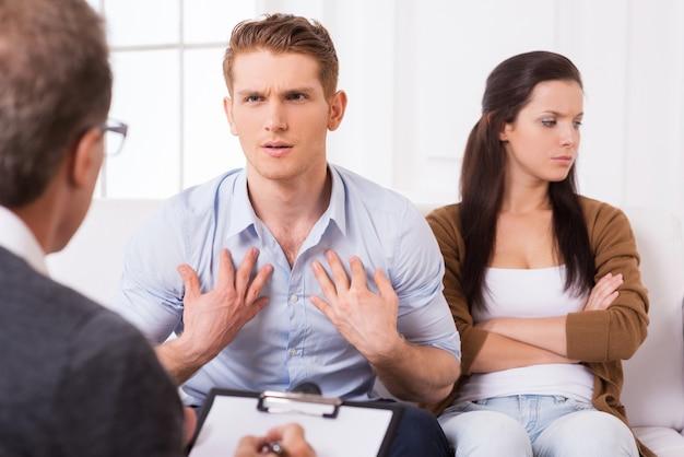 Это не моя вина! недовольный молодой человек разговаривает с психиатром и жестикулирует, в то время как его жена сидит рядом с ним и скрещивает руки