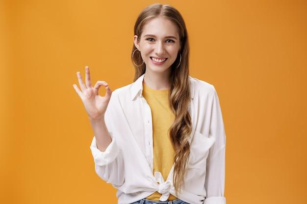 構いませんよ。 tシャツの上にトレンディなブラウスを着たウェーブのかかった髪のフレンドリーな笑顔の女の子は、オレンジ色の壁に肯定的な答えを与えることを主張し、確実に笑顔で大丈夫または完璧なジェスチャーを示しています。