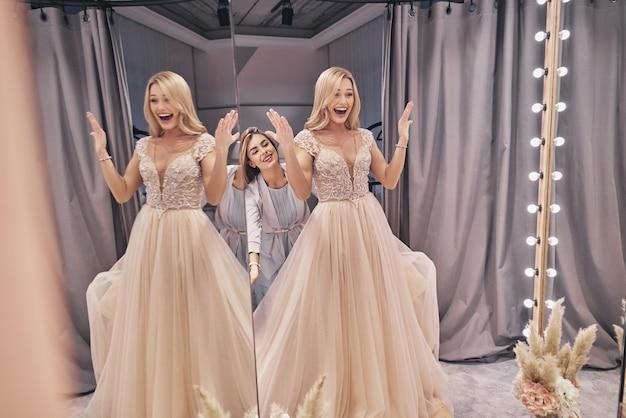 이거 완벽 해. 피팅 룸에 서 있는 동안 신부에 웨딩 드레스를 조정 하는 매력적인 젊은 여자의 반영