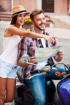 そこにあります!彼の近くに立って、彼の美しいガールフレンドと一緒にスクーターに座って地図を保持しているハンサムな若い男