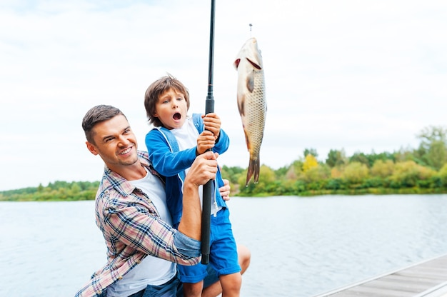 It is so big! father and son stretching a fishing rod with fish on the hook while little boy looking excited and keeping mouth open