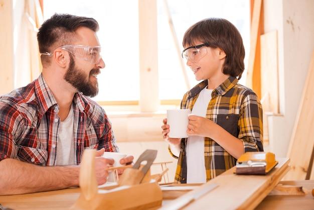 休憩の時間です。若い男性の大工と彼の息子がカップを持ってワークショップで働いている間お互いを見ている笑顔
