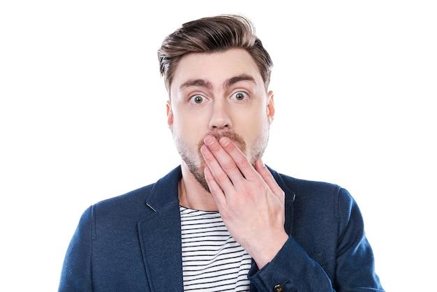 Это невероятно! портрет удивленного молодого человека, смотрящего в камеру и прикрывающего рот рукой, стоя на белом фоне