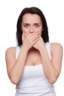 信じられない!手で口を覆い、白で孤立して立っている間カメラを見て驚いた若い女性