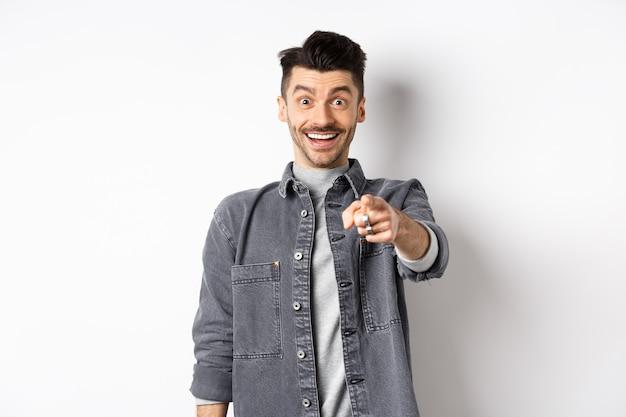 그건 너다. 쾌활 한 얼굴로 카메라에 손가락을 가리키는 흥분된 웃는 남자, 흰색 바탕에 데님 재킷에 서있는 사람을 인식합니다.