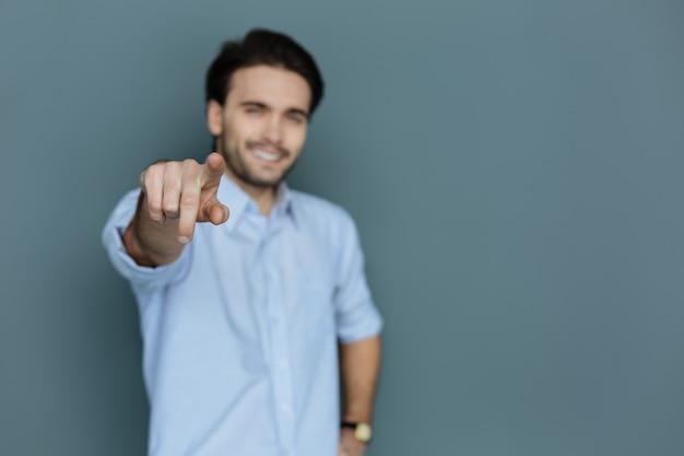 あなただ。素敵なポジティブなうれしそうな男があなたに向けている男性の指の選択的な焦点