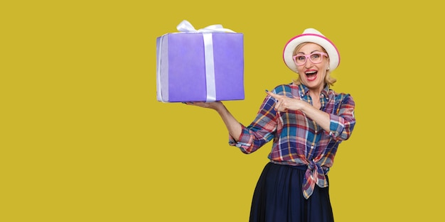 이것은 당신거야? 흰색 모자와 체크무늬 셔츠를 입은 행복한 현대 할머니는 카메라를 바라보며 손가락으로 가리키는 큰 선물 상자를 들고 놀랐습니다. 노란색 배경에 스튜디오 촬영