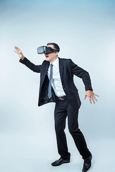 それはとてもリアルに見えます。特別なヘッドセットを背景に装着し、vrゲーム中に驚いて身振りで示すサラリーマンの全身ショット。