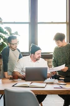 Ит-специалист разговаривает со своими коллегами в офисе