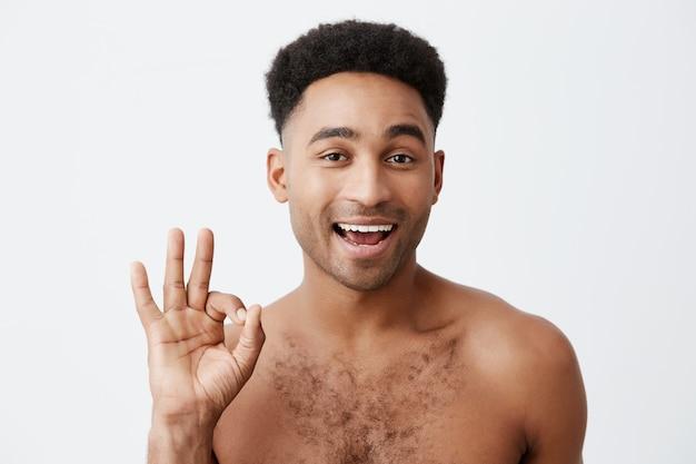 Ok. non ti preoccupare. chiuda in su di giovane uomo dalla pelle scura attraente allegro con l'acconciatura afro con il torso nudo che mostra il segno giusto con la mano, sbatte le palpebre, guardante a porte chiuse con l'espressione civettuola.