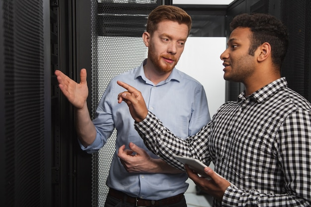 It problem. professional it technicians talking and pointing at hardware