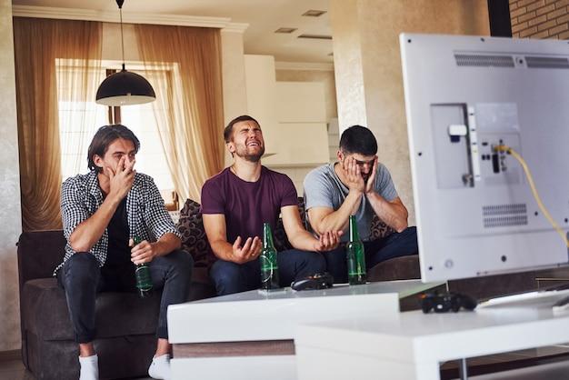 Это поражение. грустно трое друзей вместе смотрят футбол по телевизору дома.