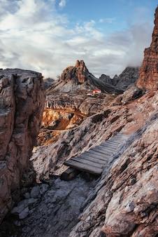 Это долгий путь. экстремальная тропа по краю холмов с деревянным мостиком на дорогу к зданию, стоящему у доломитовых гор.
